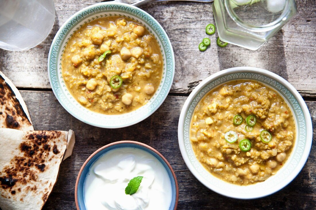 Two bowls of chana masala (chickpea curry) with unleavened bread and raita