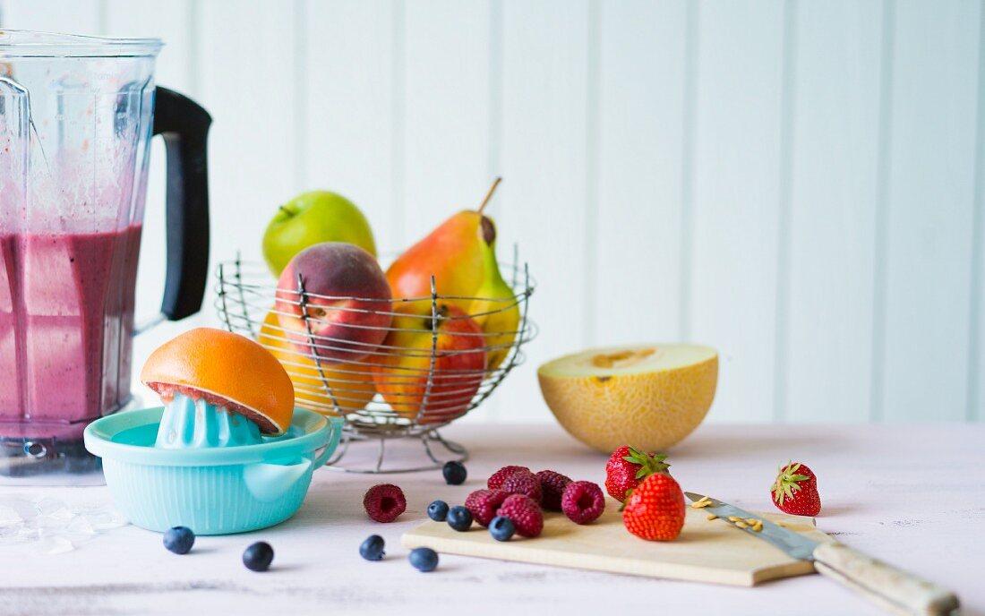 Arrangement of various fruits, a juicer, and a mixer
