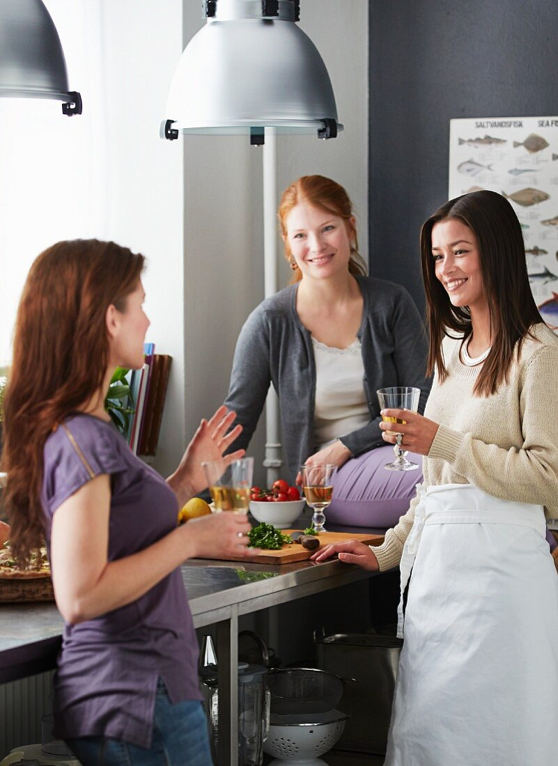 Three friends in a kitchen with drinks