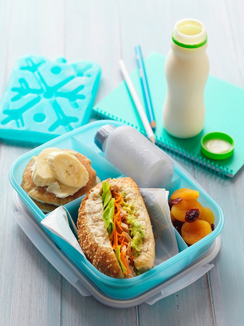 A lunchbox with a tuna fish and avocado sandwich, dried fruits and mini pancakes