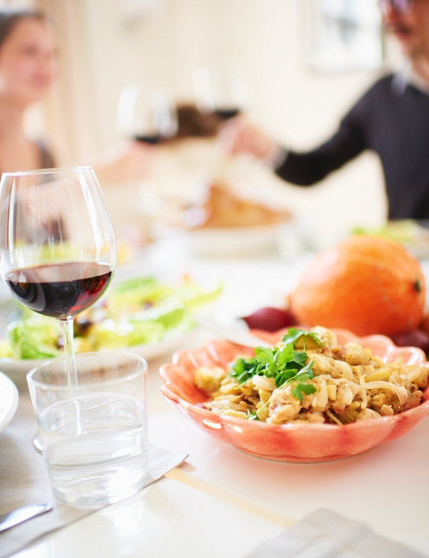 A couple raising a toast with glassed of red wine at a table laid for Thanksgiving