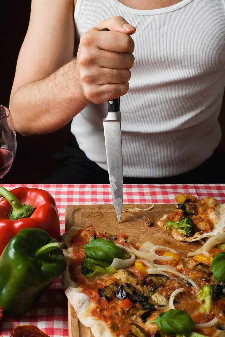 A typical Italian man stabbing his knife into a chopping board next to a pizza