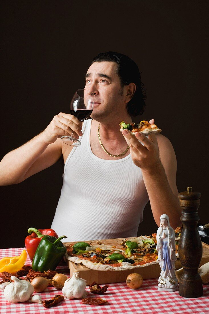 A stereotypical Italian man eating pizza and drinking red wine
