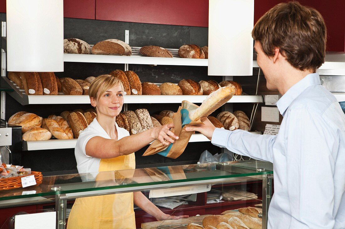 A sales assistant in a bakery handing a customer a baguette
