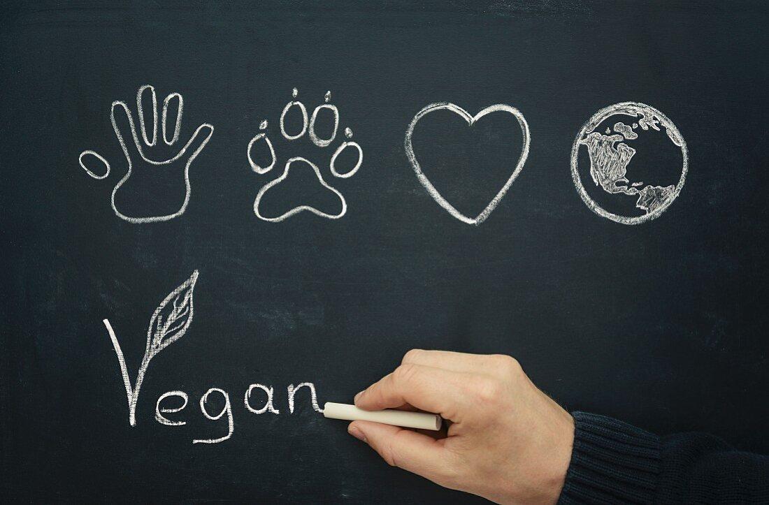 A hand writing the word 'Vegan' on a blackboard