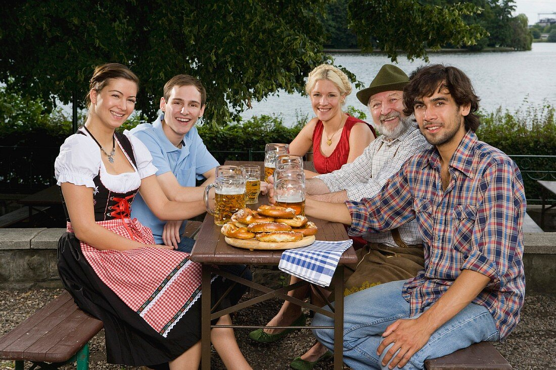 Five people sitting in a beer garden at a table with tankards and pretzels