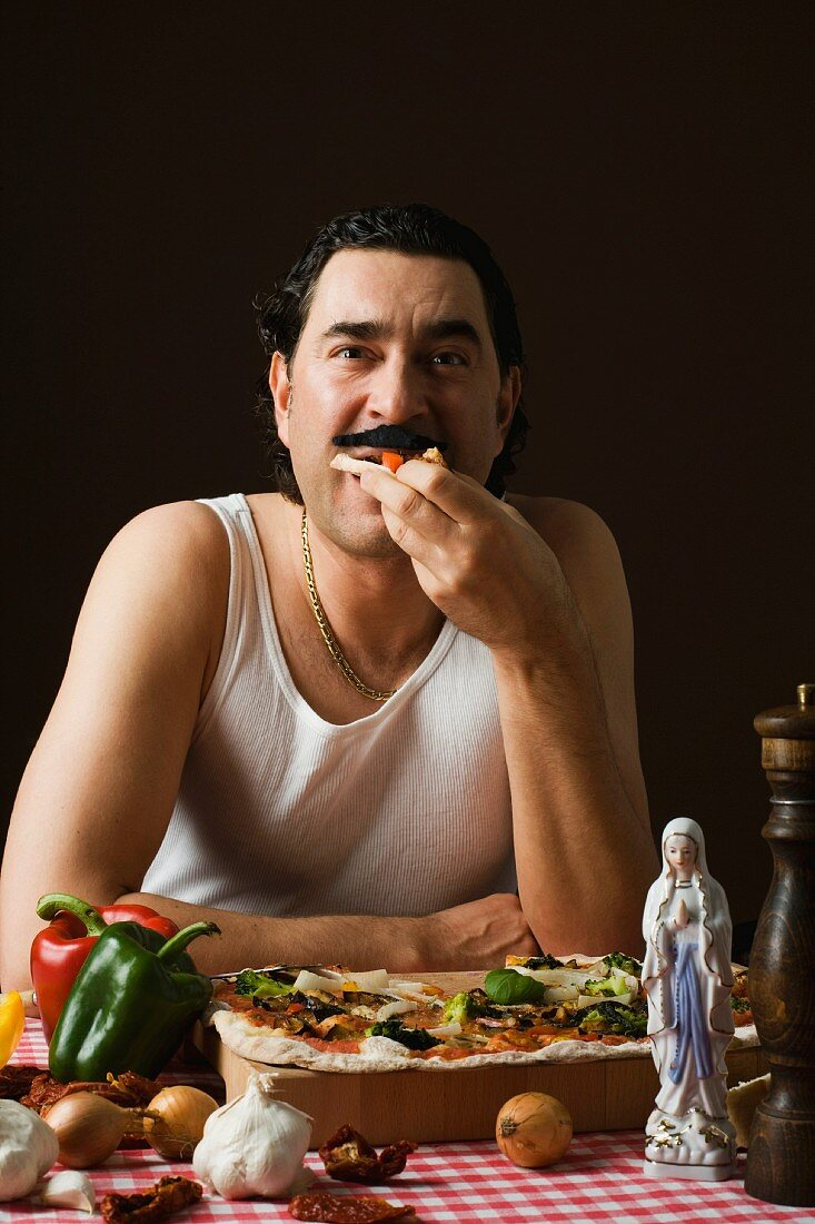 A stereotypical Italian man eating pizza