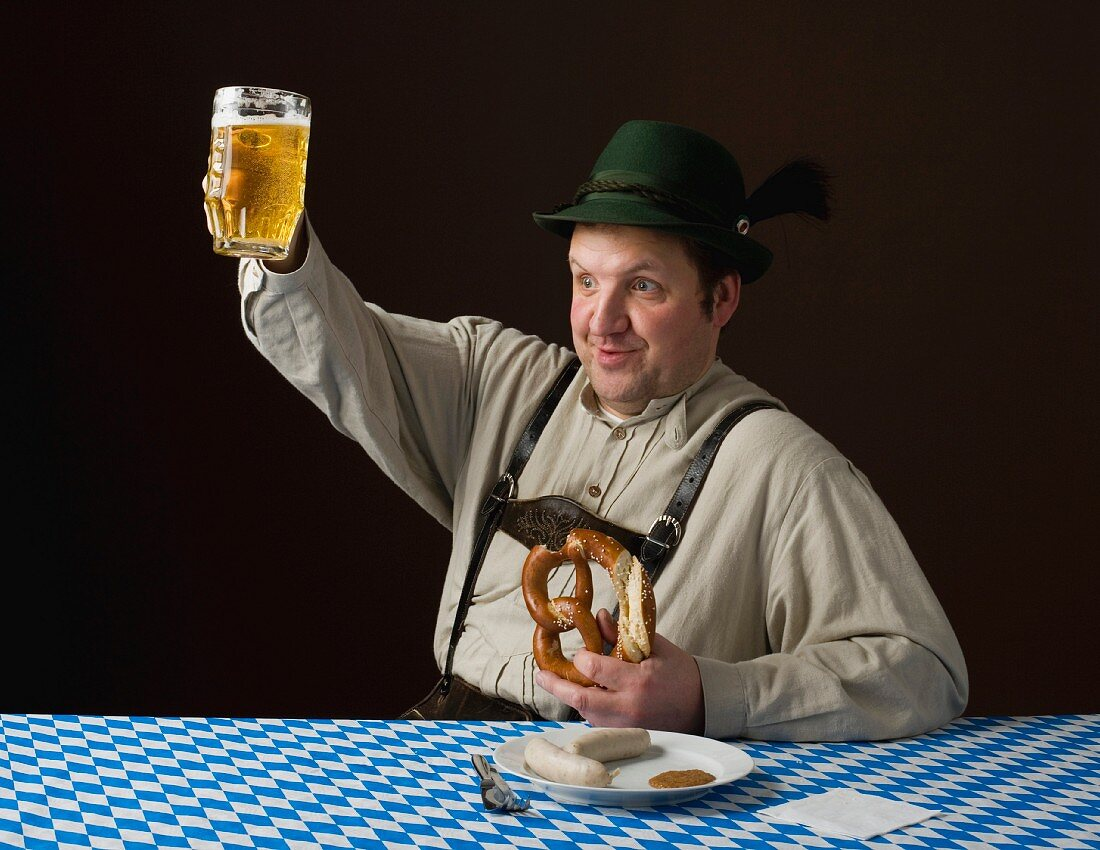 A stereotypical German man wearing lederhosen and eating a pretzel and white sausage with a beer