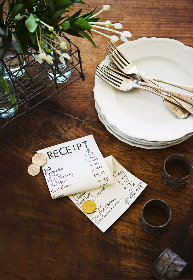 Cake plates with silver forks, decorative flowers in a wire basket and a bill on an old wooden table