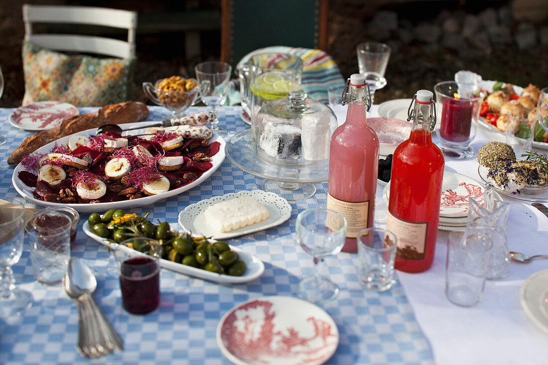 A table laid in a garden with goat's cheese, preserved pears, olives, bread and drinks