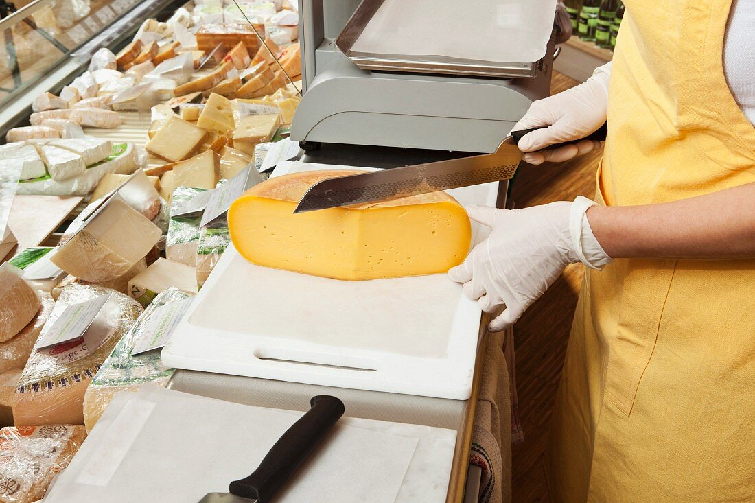 A sales assistant slicing cheese at the cheese counter