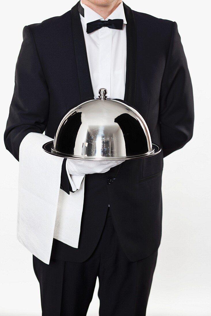 A butler holding a cloche