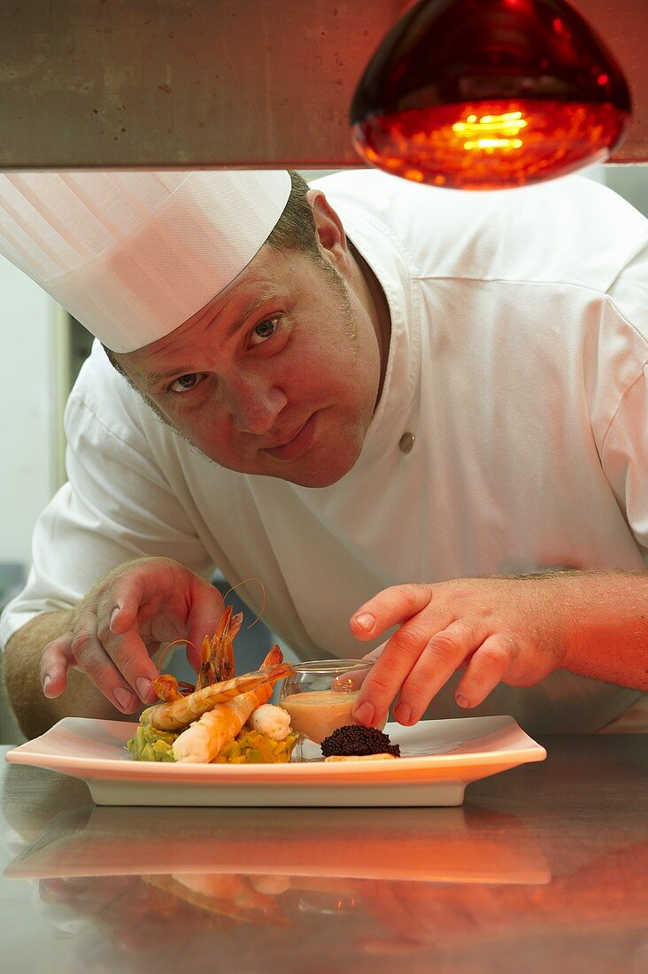 A head chef serving prawns on avocado tartar with a dip