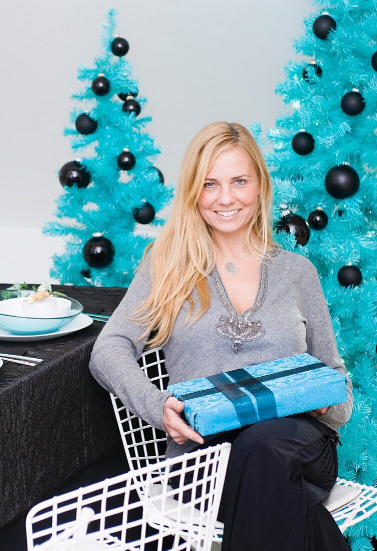 A blonde woman with a Christmas present