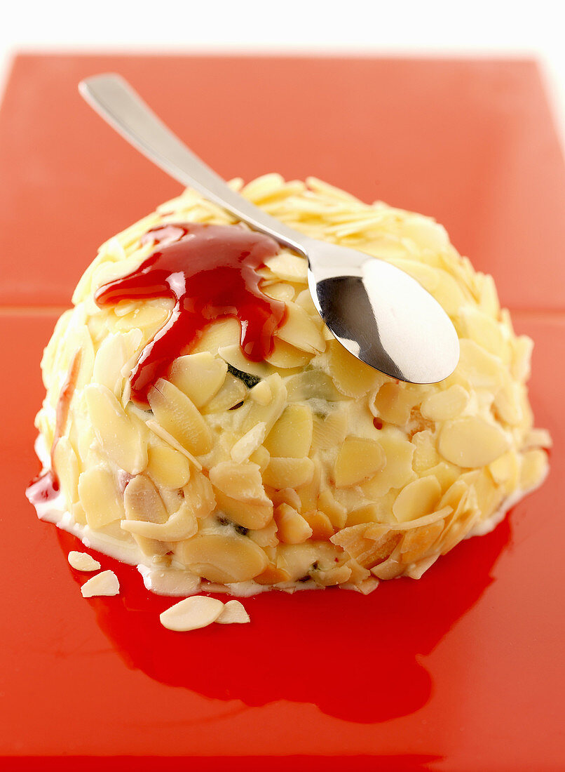 A vanilla ice cream bomb with slivered almonds and fruit sauce