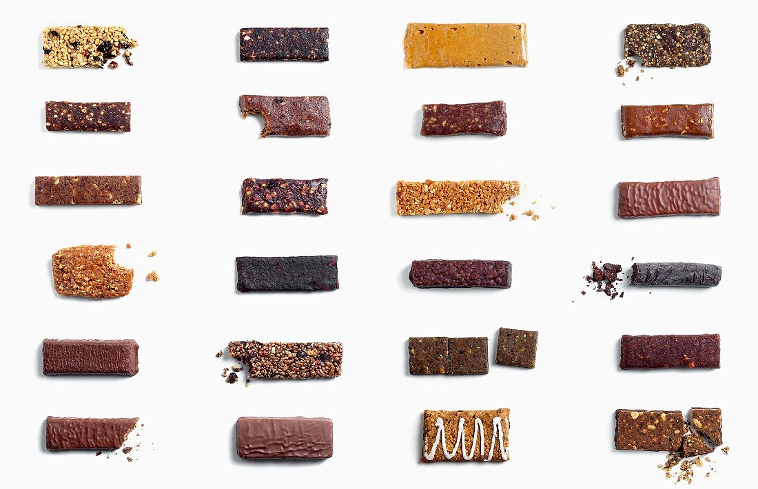 Large Assortment of Granola Bars on White Background; Some Crumbled and Bitten