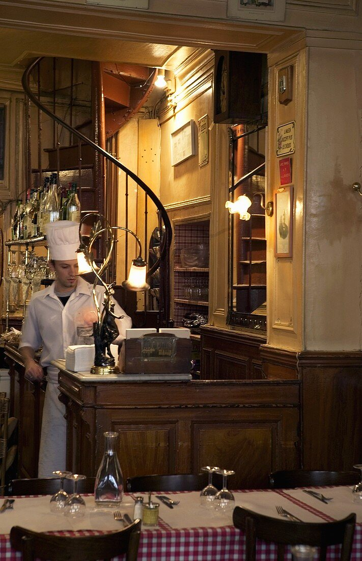 A chef standing in the reception of a restaurant