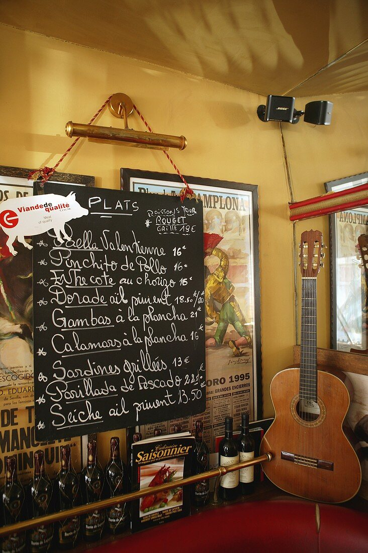 A menu on a blackboard next to a guitar in a Spanish bistro