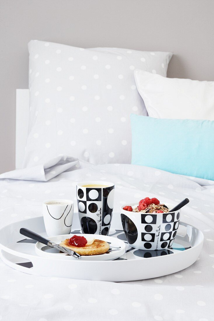 Muesli, toast with jam, coffee and orange juice on a breakfast tray on a bed