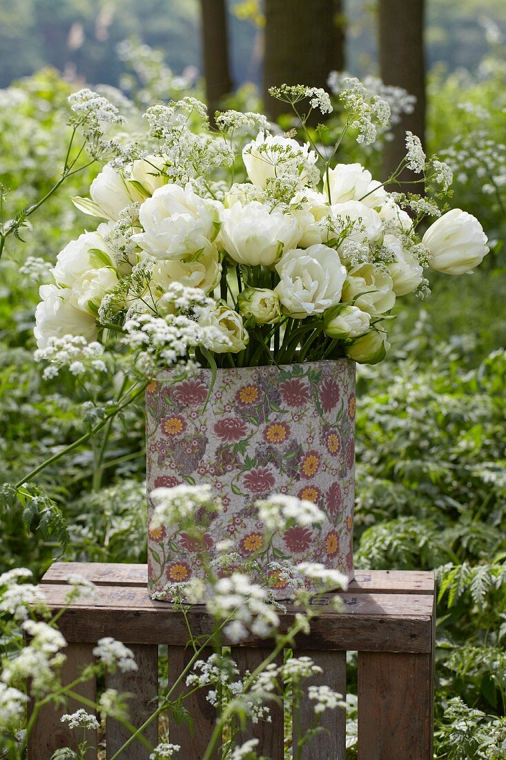 A bunch of white tulips (tulipa Maureen Double) in a vase in a garden