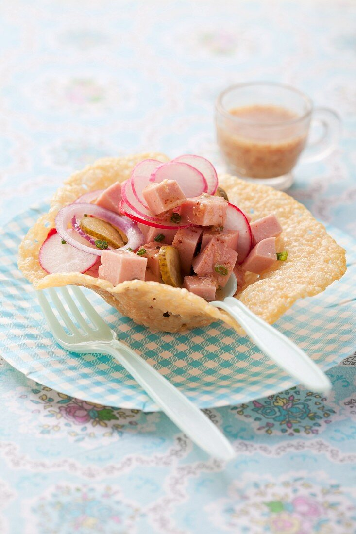 Sausage salad with radishes in a Parmesan bowl