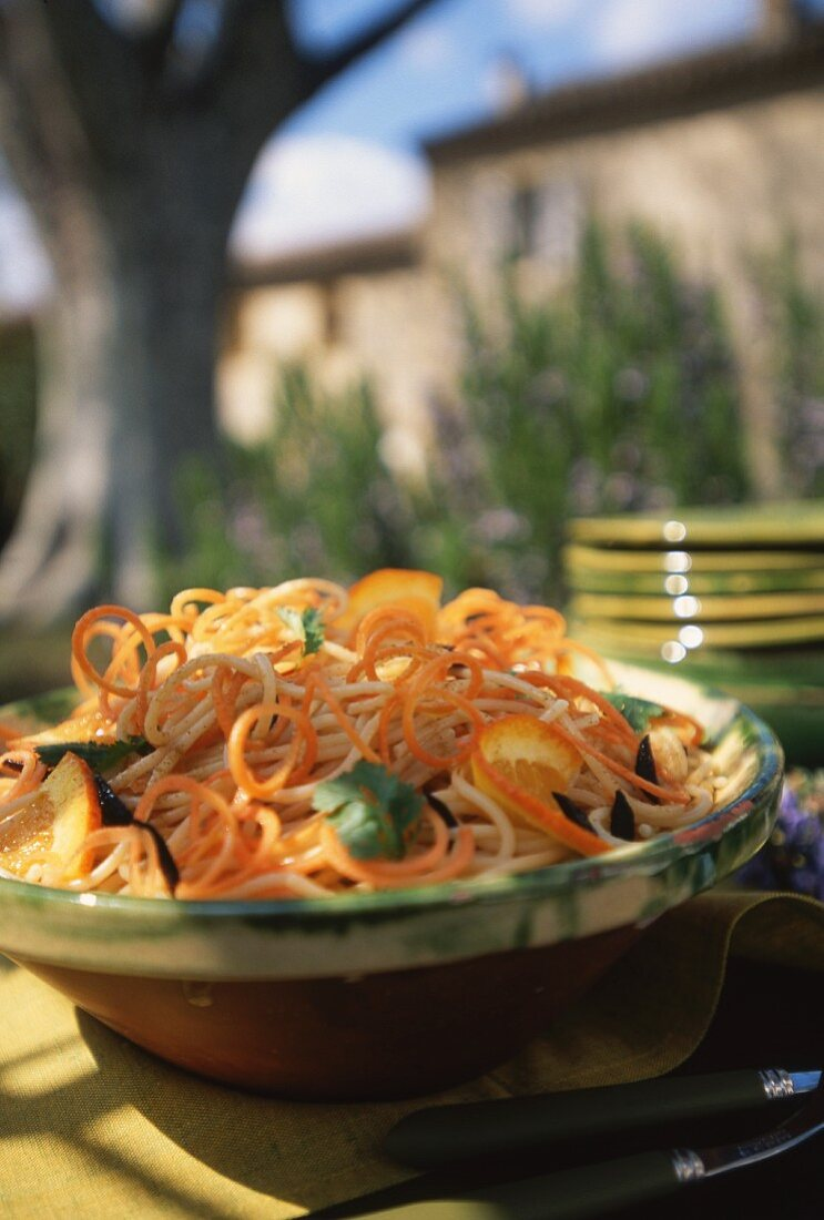 Spaghettoni with carrots and oranges on a table in the open air