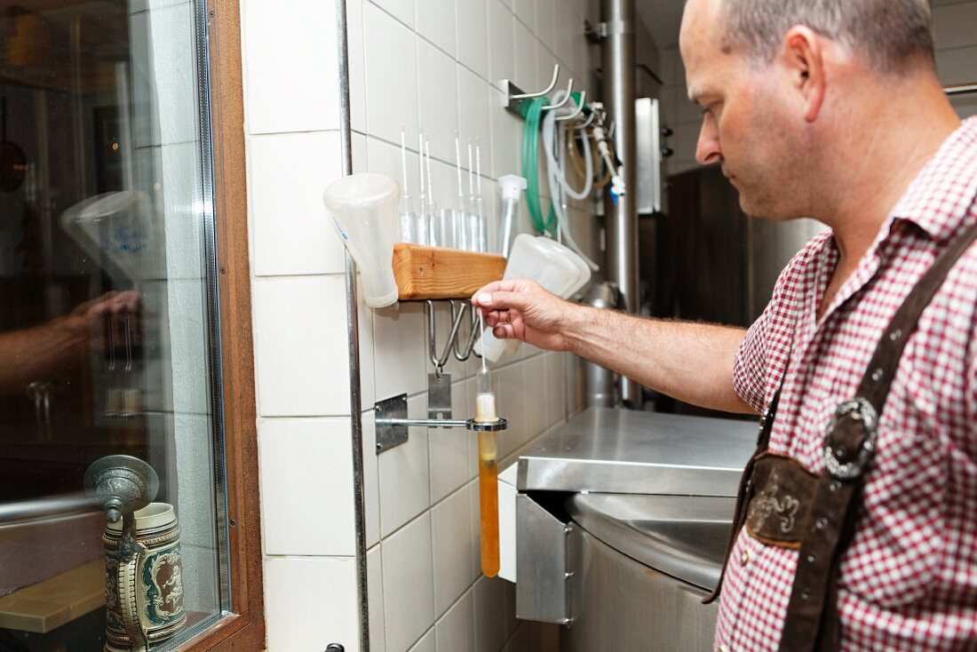 A brewer measuring the density of beer with a hydrometer