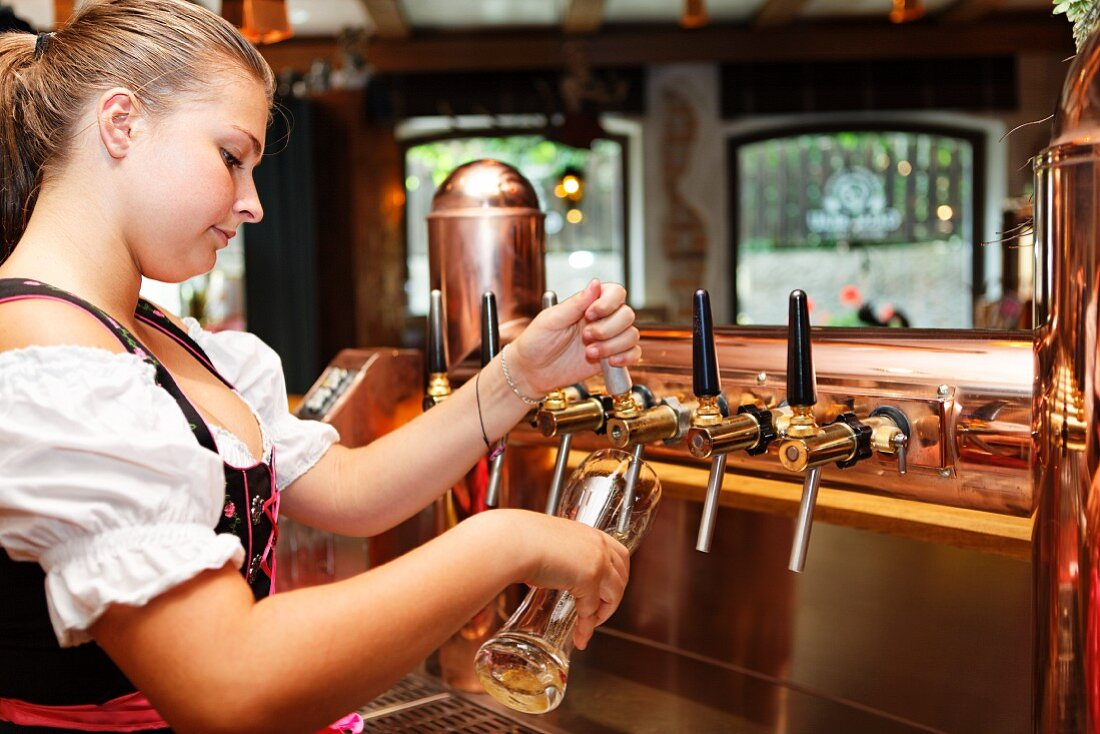 A barmaid tapping a glass of wheat beer