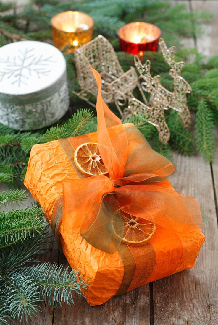 A Christmas present decorated with a bow and dried orange slices
