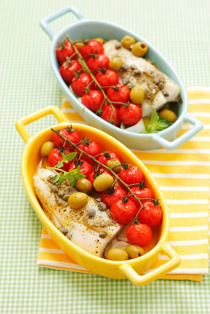 Halibut with cherry tomatoes, olives and capers in baking dishes
