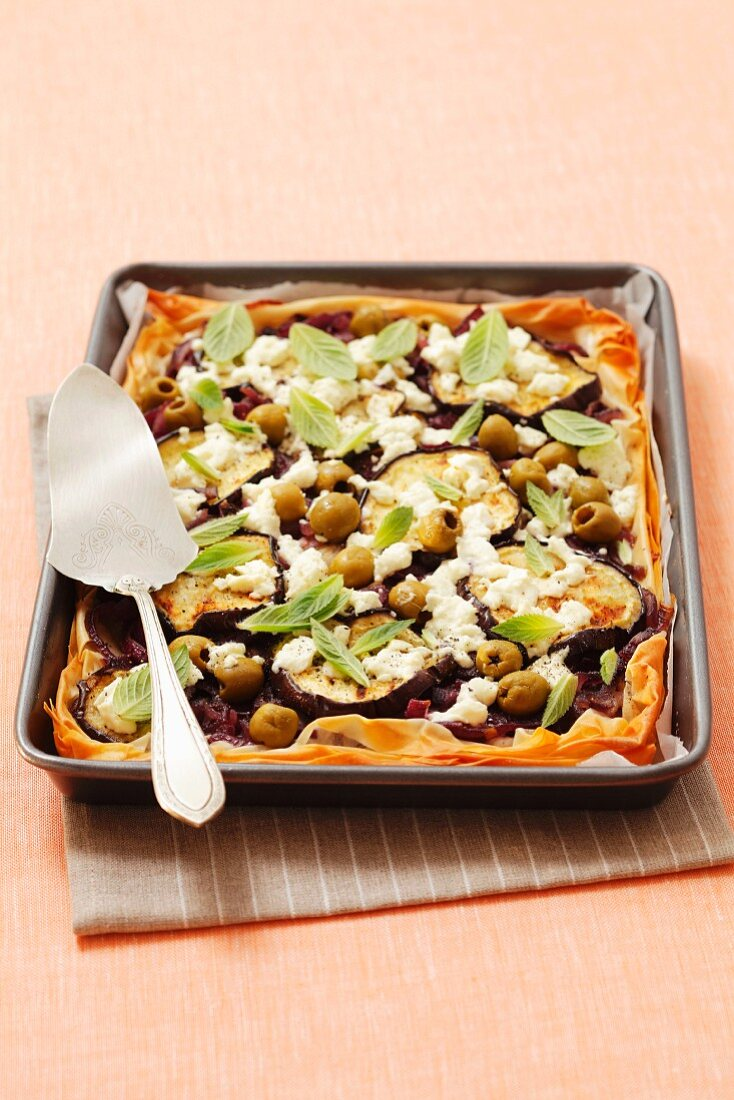 A puff pastry part topped with aubergines, olives, caramelised onions and feta cheese