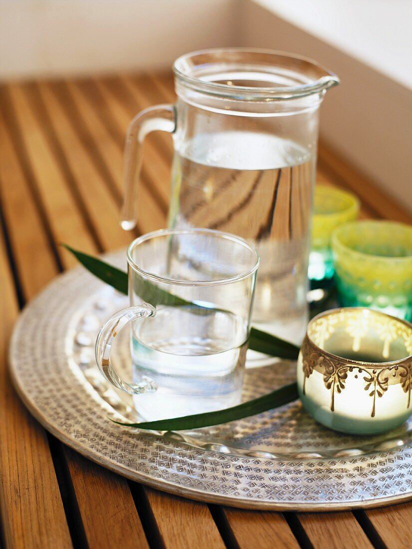 A jug of water and a glass on a sliver tray