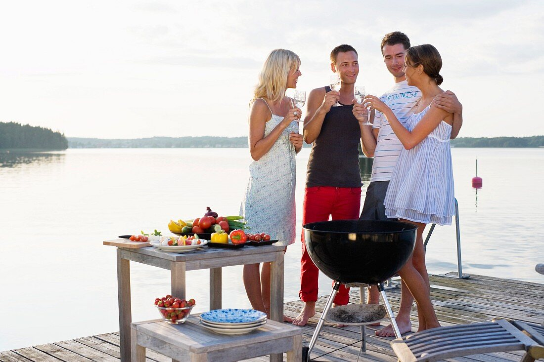 People barbecuing on a jetty by a lake