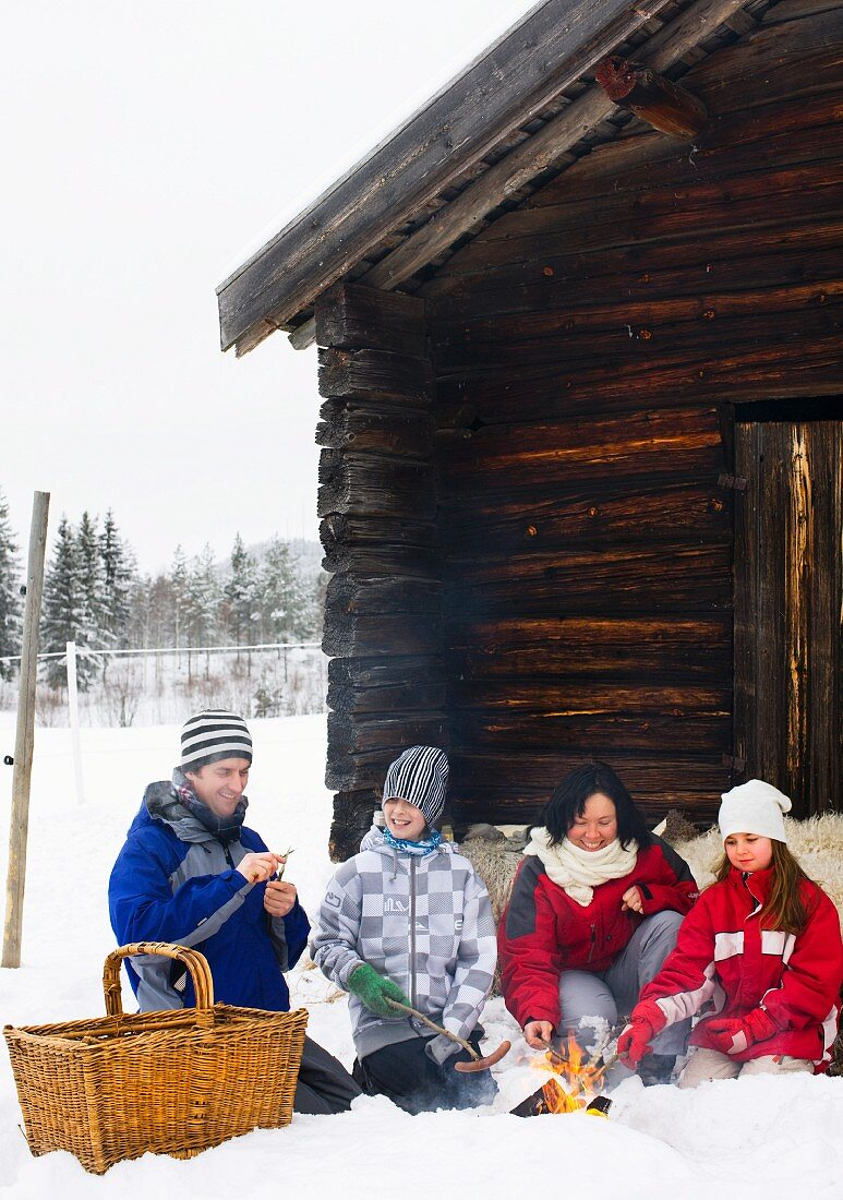 A family grilling sausages on a open fire in front of a mountain hut