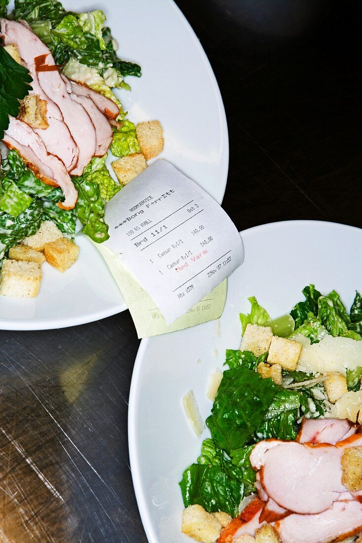 Two plates of salad in a restaurant kitchen