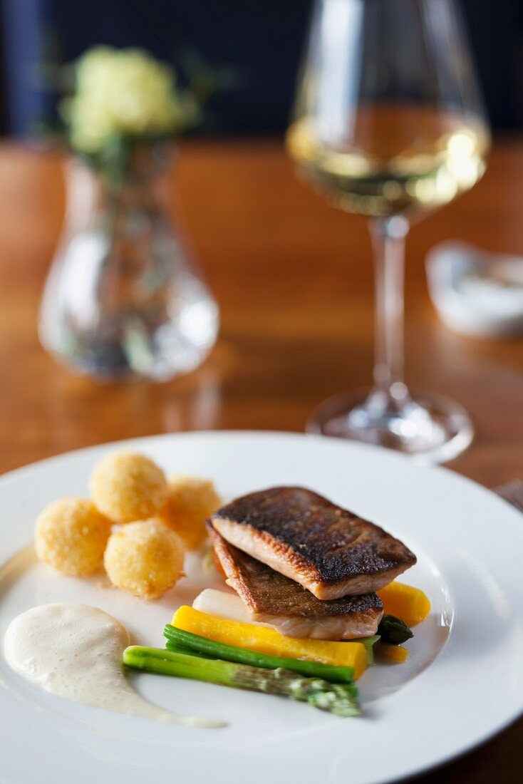 Fried char fillet with potato and almond croquettes and vegetables