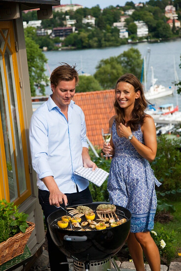Couple next to barbecue with lamb chops, artichokes and lemons