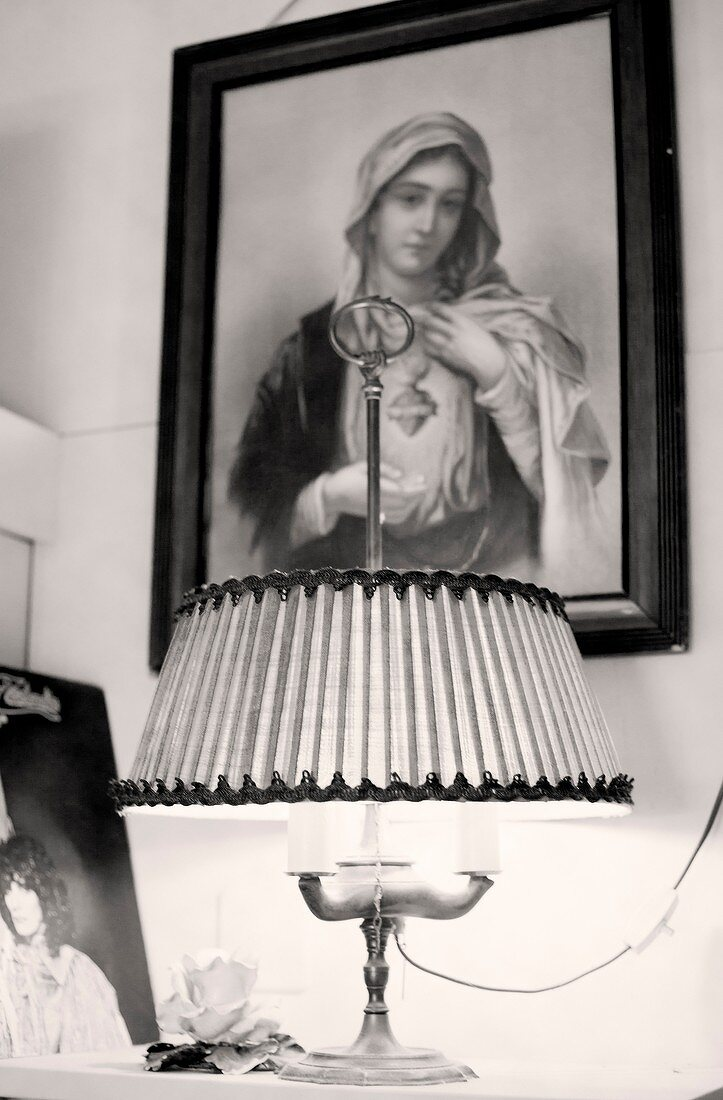 Religious picture hangs above bedside table with lamp