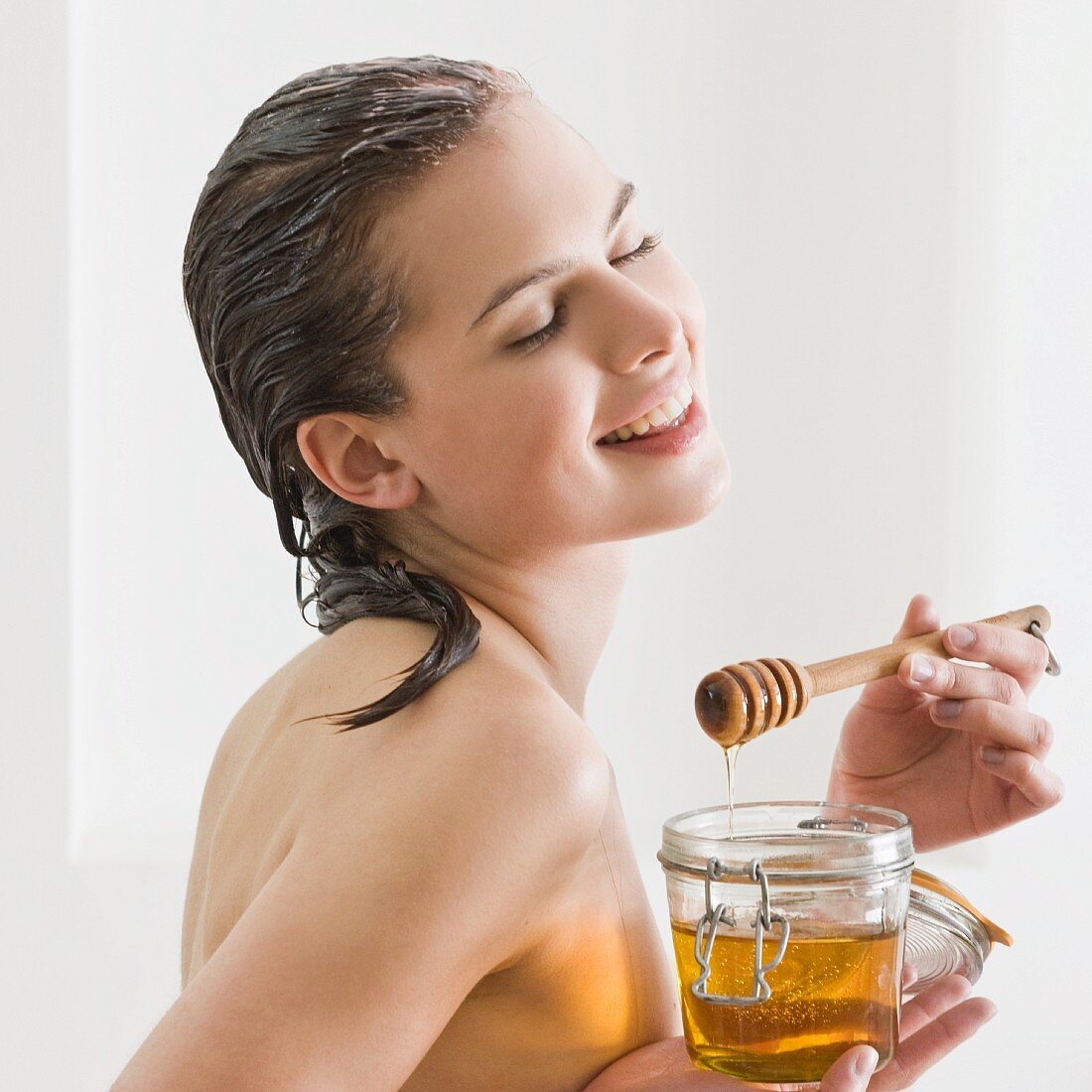 A young woman with a jar of honey and a honey spoon