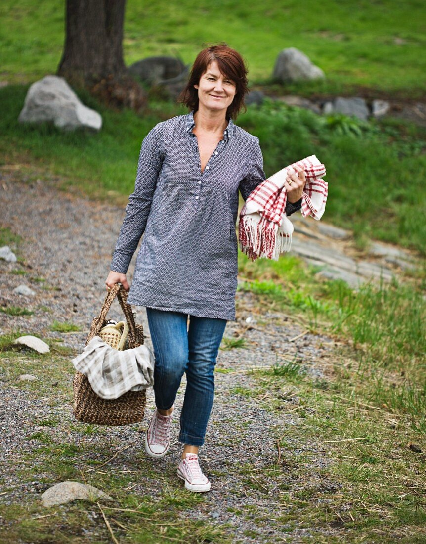 A woman carrying a picnic basket and a blanket