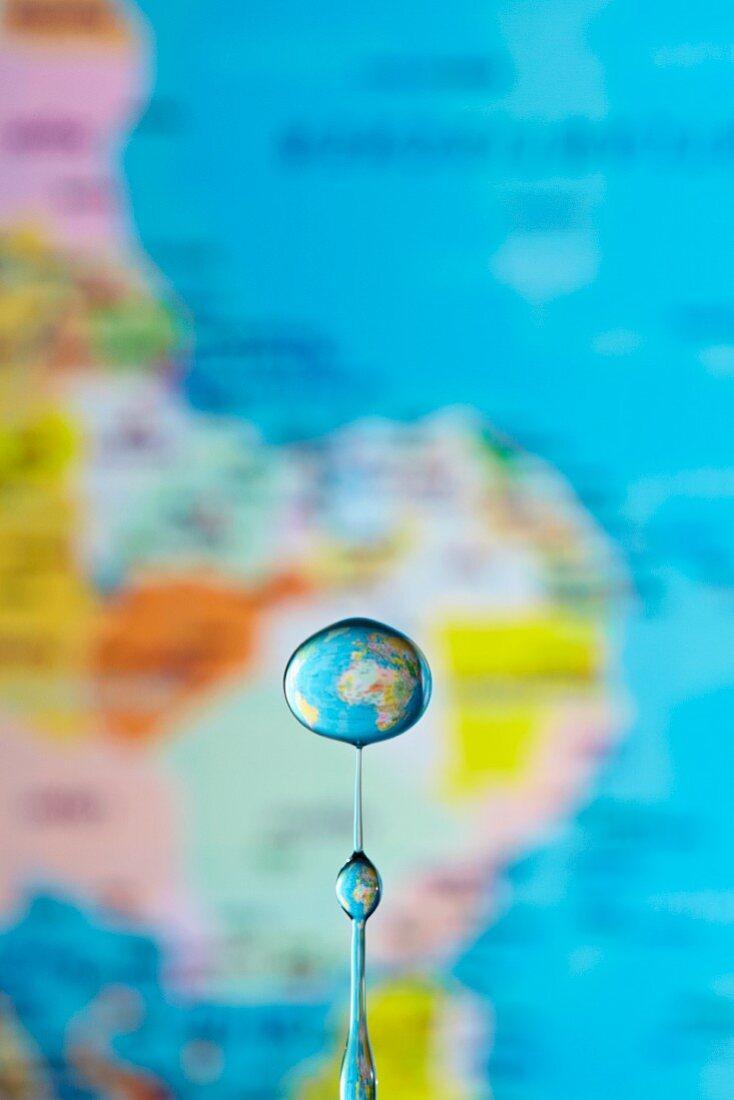 An artistic shot of a globe seen though a drop of water