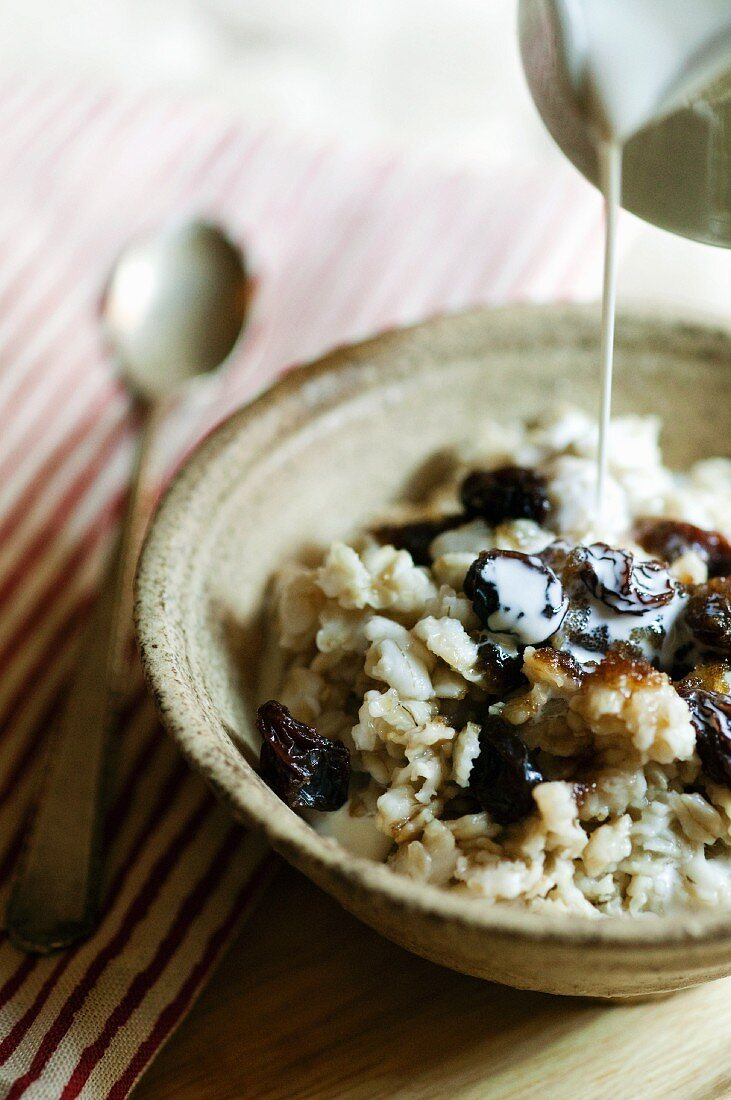 Milk Pouring Over a Bowl of Oatmeal with Raisins and Brown Sugar