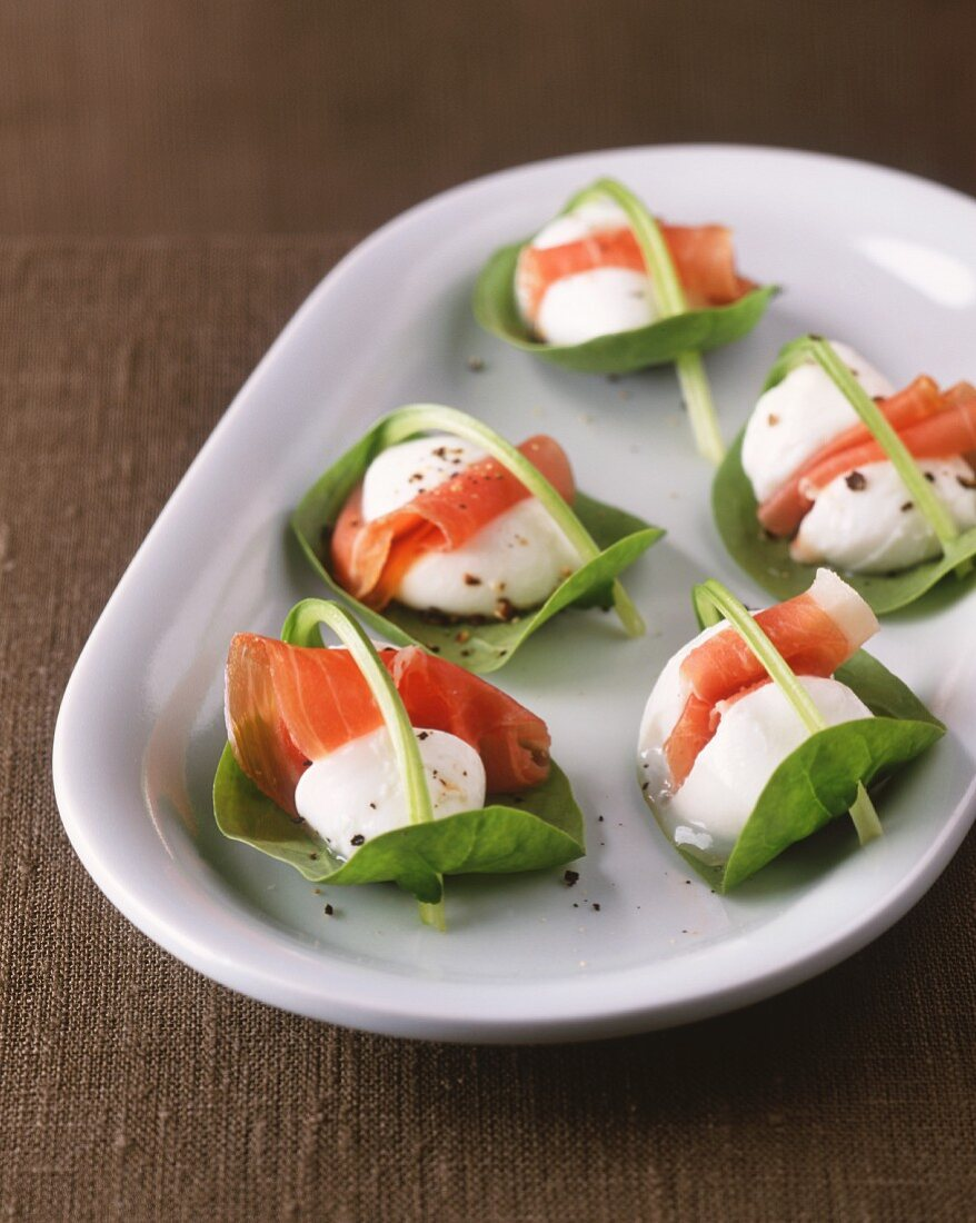 Mozzarella and Parma ham on spinach leaves