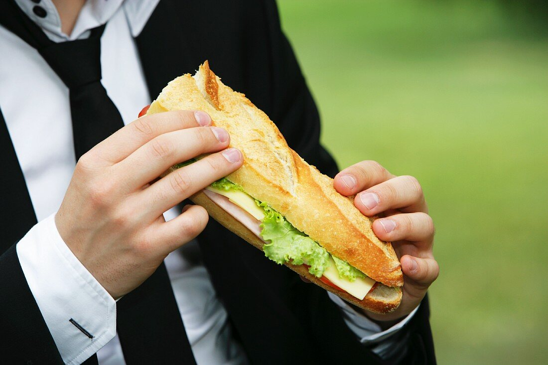 Young man eating baguette sandwich