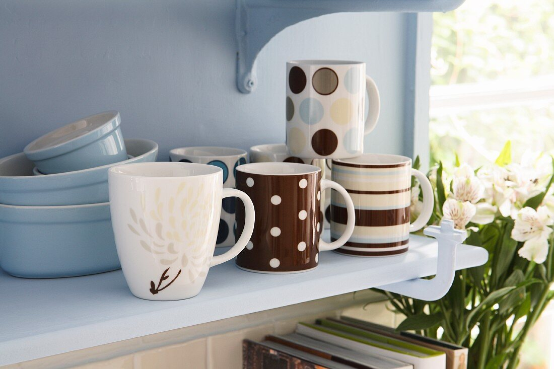 Cups and baking dishes on a shelf in a kitchen