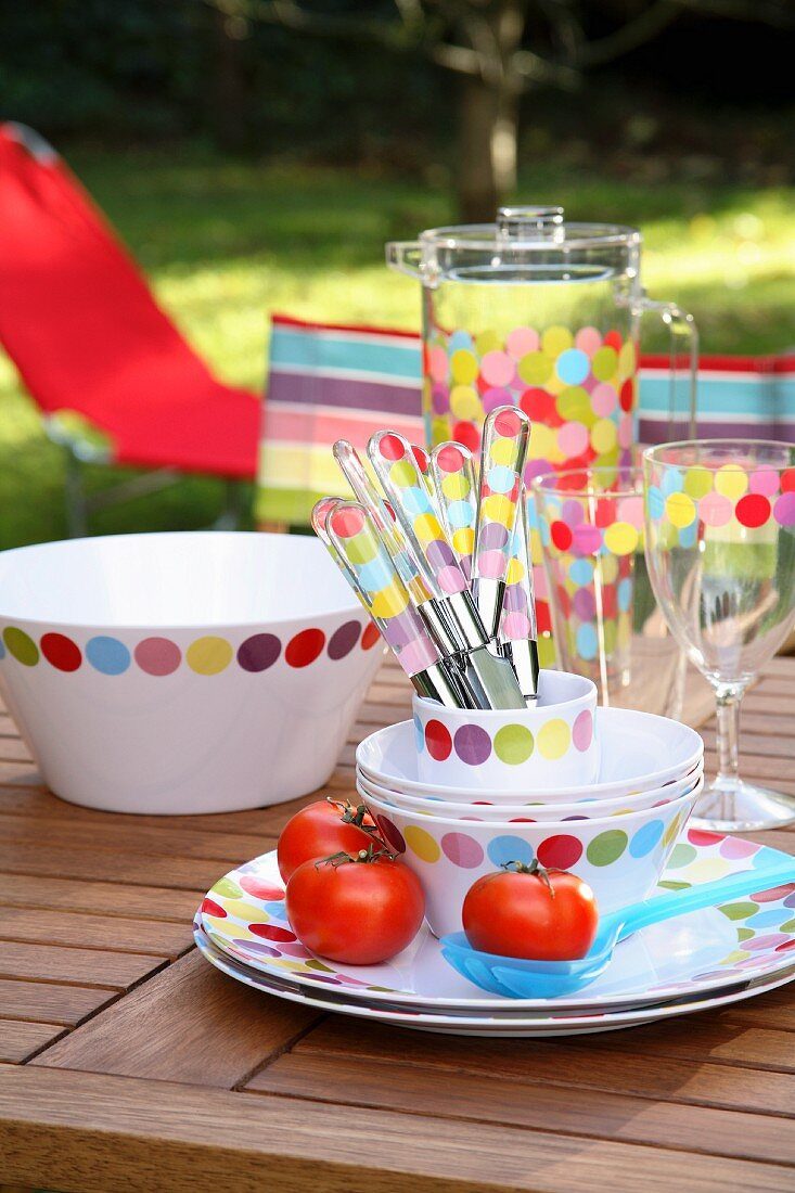 Colourful, spotted crockery and cutlery on a table in the open air