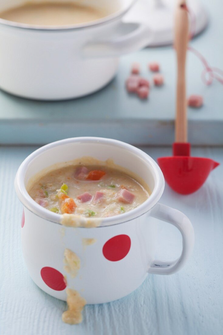 Mug of vegetable soup with cubes of ham