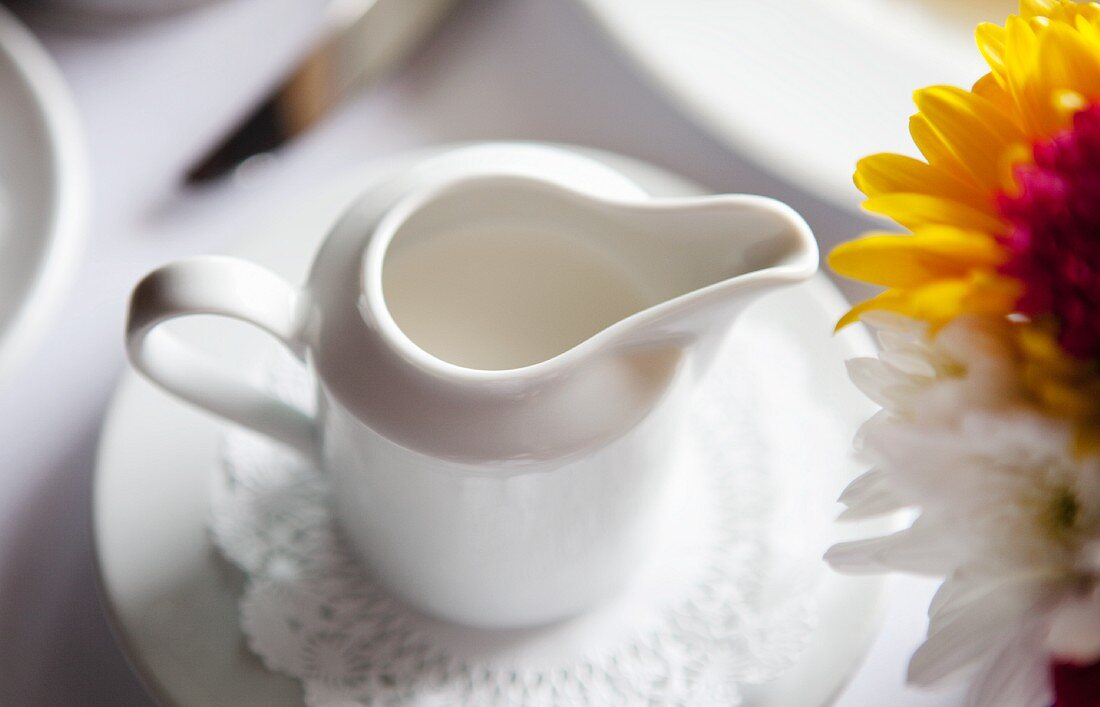 Pitcher of Cream on a Table; Flowers