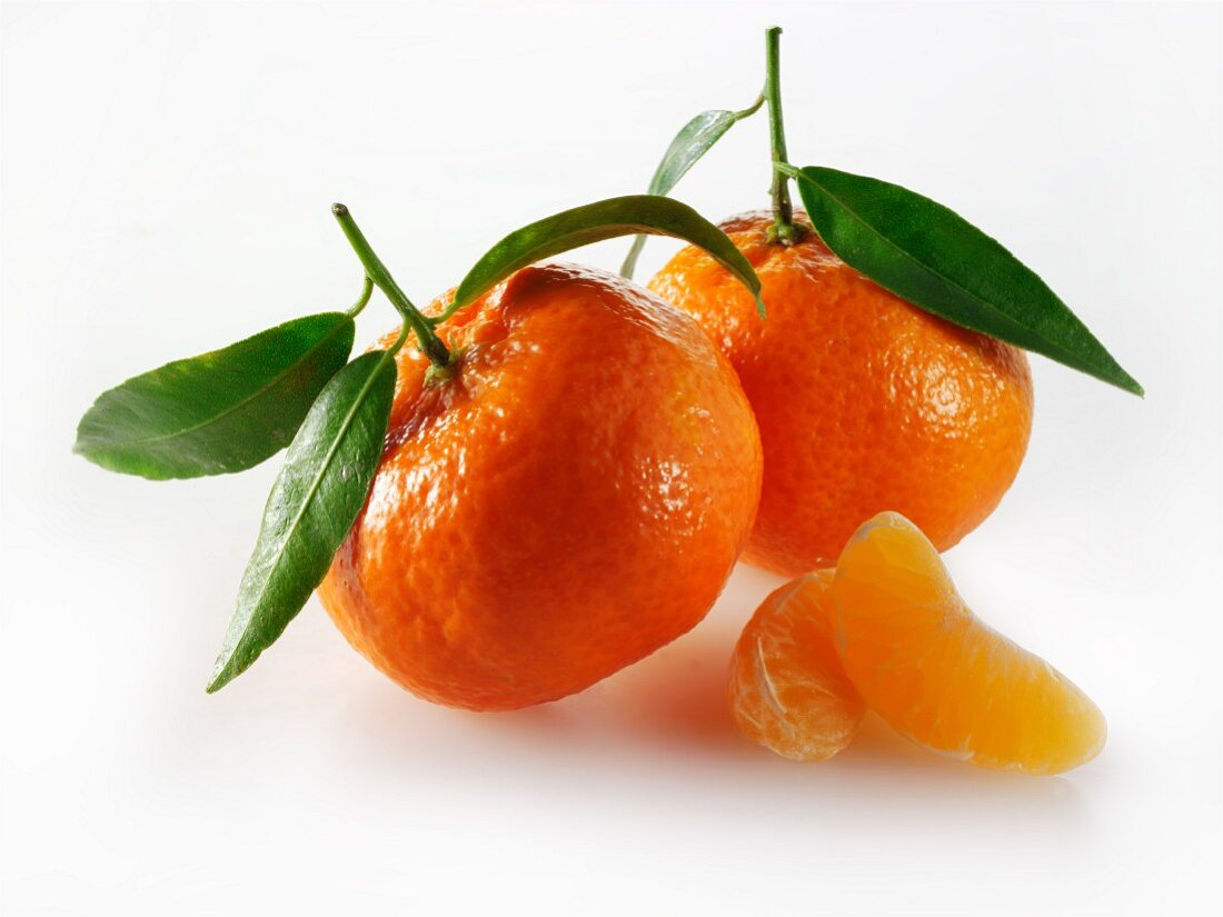 Two whole clementines with leaves and two clementine sections