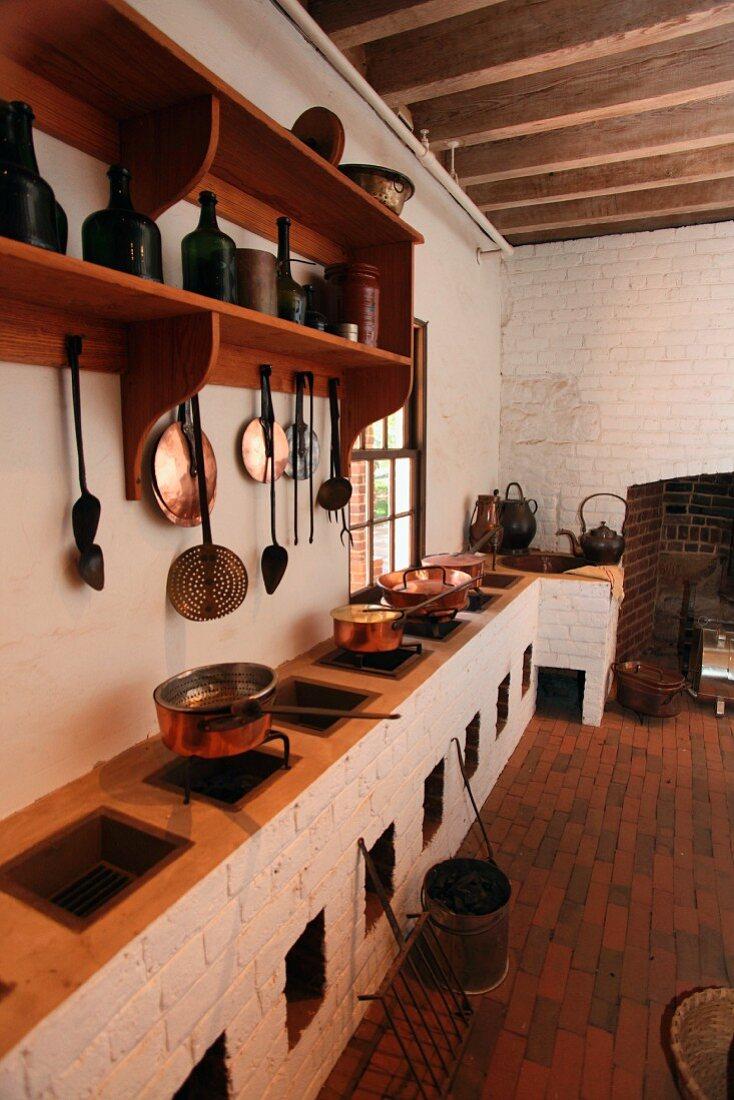 Rustikale Küche mit mehreren Feuerstellen in gemauerter Küchenzeile und Kochgeschirr aus Kupfer